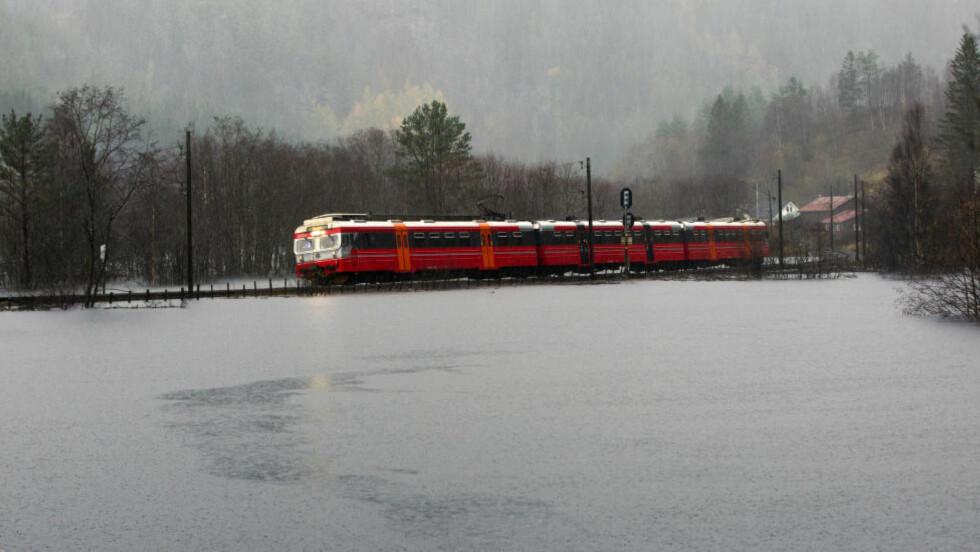 STENGT: Ved Bolstadøyri måtte togene kjøre sakte på grunn av flommen. Her går siste toget over flomvannet før Bergensbanen ble stengt. Foto: Vidar Herre / Hordaland / NTB scanpix