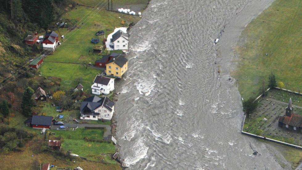 HOLDER STAND:  Inntil videre holder det gamle steingjerdet som omkranser Flåm kirke vannet fra flommen utenfor gravplassen. Foto: Hans O. Torgersen / Aftenposten / NTB Scanpix