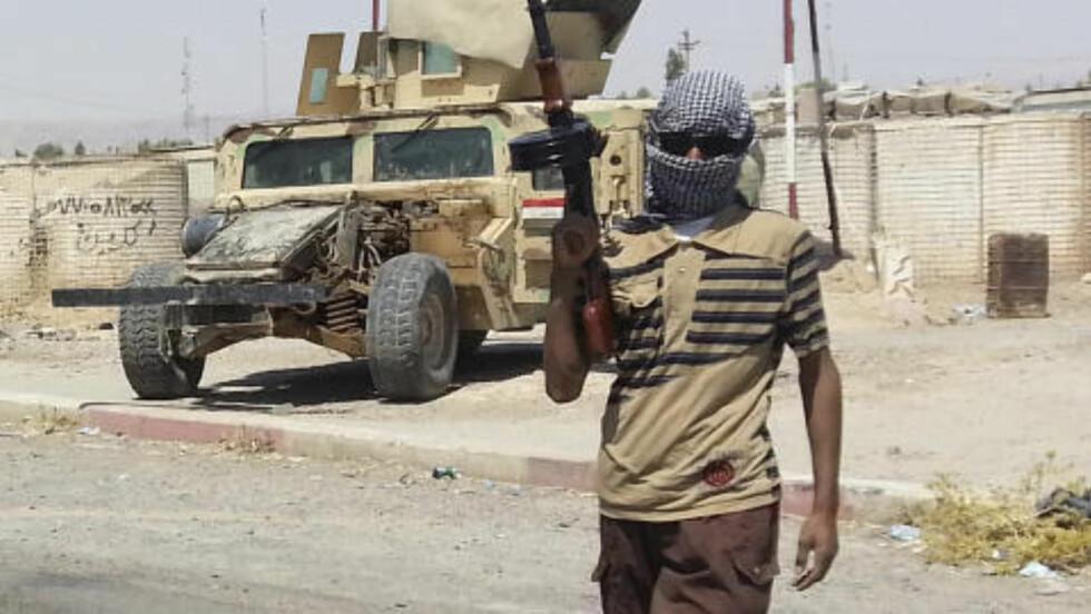 VAKT: Her står et medlem av ISIL vakt ved grensen nær byen Baiji, der Iraks største oljeraffineri befinner seg. Foto: REUTERS/Stringer/NTB scanpix