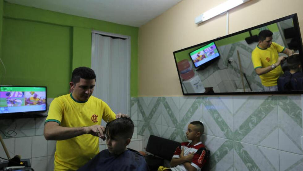 HÅRIDOL: Nettet florerer av bruksanvisninger på hvordan du får Neymars hår. Her ser vi en brasiliansk frisør gi et barn Neymar-stilen. Foto: AP Photo/Leo Correa