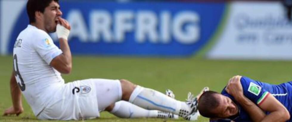 NY BITTSKANDALE: Her holder Luis Suárez seg i gebisset - mens Giorgio Chiellini holder seg til skuldra. Den første, og sannsynligvis den største, skandalen i fotball-VM 2014 er et faktum. Foto: Javier Sorano / AFP / NTB Scanpix