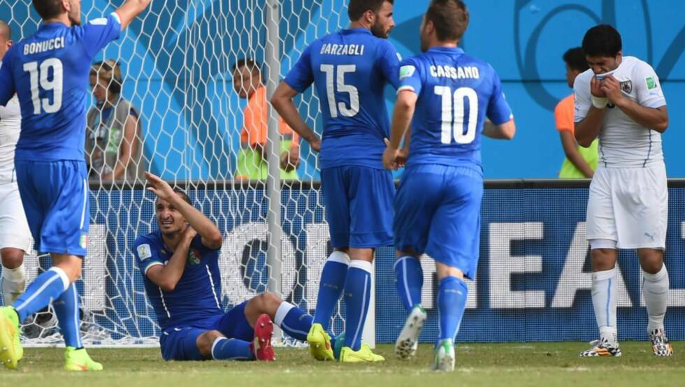 VONDT: Både Luis Suarez og Giorgio Chiellini så ut til å ha smerter etter tennene til førstnevnte hadde møtt skulderen til italieneren. Men det er nok mannen lengst til høyre i bildet som får den strengeste straffen. Foto: AFP PHOTO / EMMANUEL DUNAND / NTB Scanpix