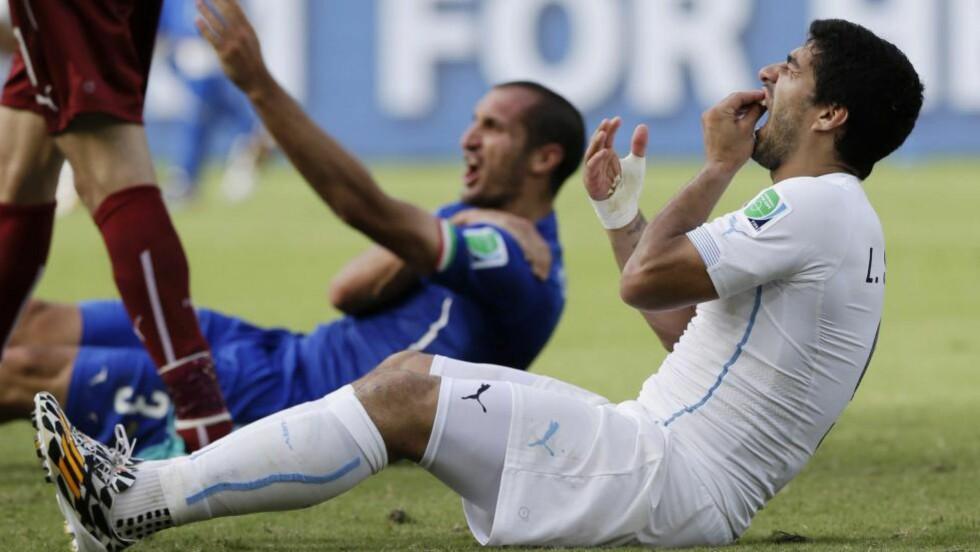 BITTET I NATAL: Luis Suarez sjekker tenna sine etter å ha bitt Italias midtstopper Giorgio Chiellini under VM-kampen i Natal i går. Dommeren fikk ikke med seg episoden, og delte dermed ikke ut kort for bitingen, men Suarez har frist til klokka 22 i kveld, norsk tid, med å komme med sin versjon til FIFA. Han kan trolig vente seg en lengre utestengelse. Foto: Ricardo Mazalan / AP / NTB Scanpix