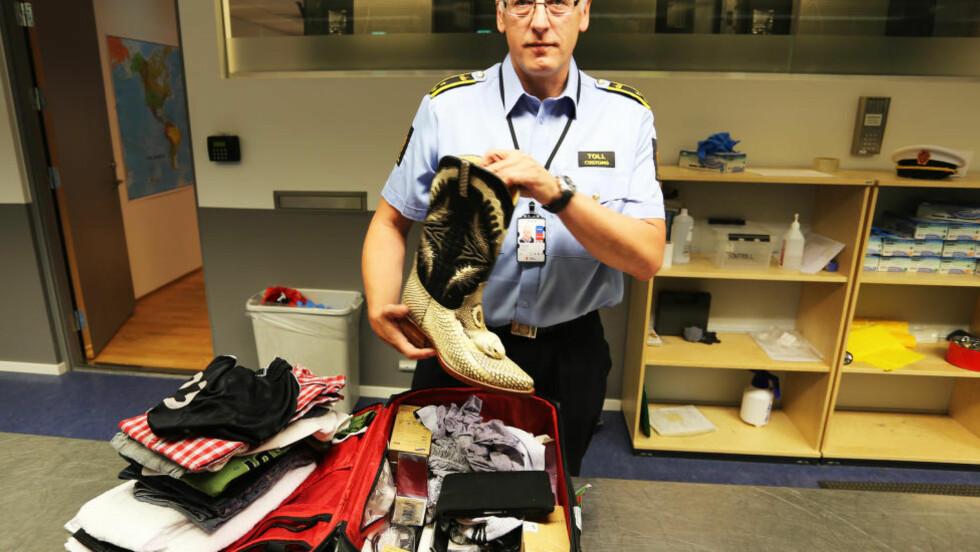 IKKE KJØP ULOVLIGE SUVENIRER: Tor Fredriksen, kontorsjef for Tollvesenet på Oslo lufthavn, viser fram beslag av ulovlige slangeskinnsprodukter. Foto: OSLO LUFTHAVN AS