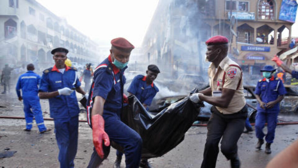 MISTENKER TERRO:  Politiet mistenker at eksplosjonen skyldes terror. Her bæres en av de døe bort fra åstedet. Foto: AP Photo/Olamikan Gbemiga