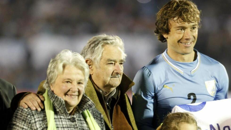 FORSVARER: Uruguays president, Jose Mujica (i midten) forsvarer Luis Suarez etter biteepisoden. Her er han sammen med blant andre landslagsspilleren Diego Lugano og kona Lucia Topolansky under en av Uruguays forberedende kamper til verdensmesterskapet. Foto: EPA/IVAN FRANCO
