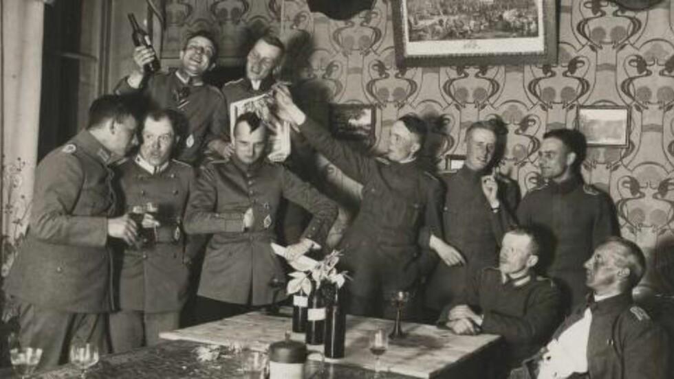 LYSTIG LAG: Tyske offiserer svinger glassene og synger - mens den ene av dem etterligner Napoleon. Foto: Odette Carrez/Reuters