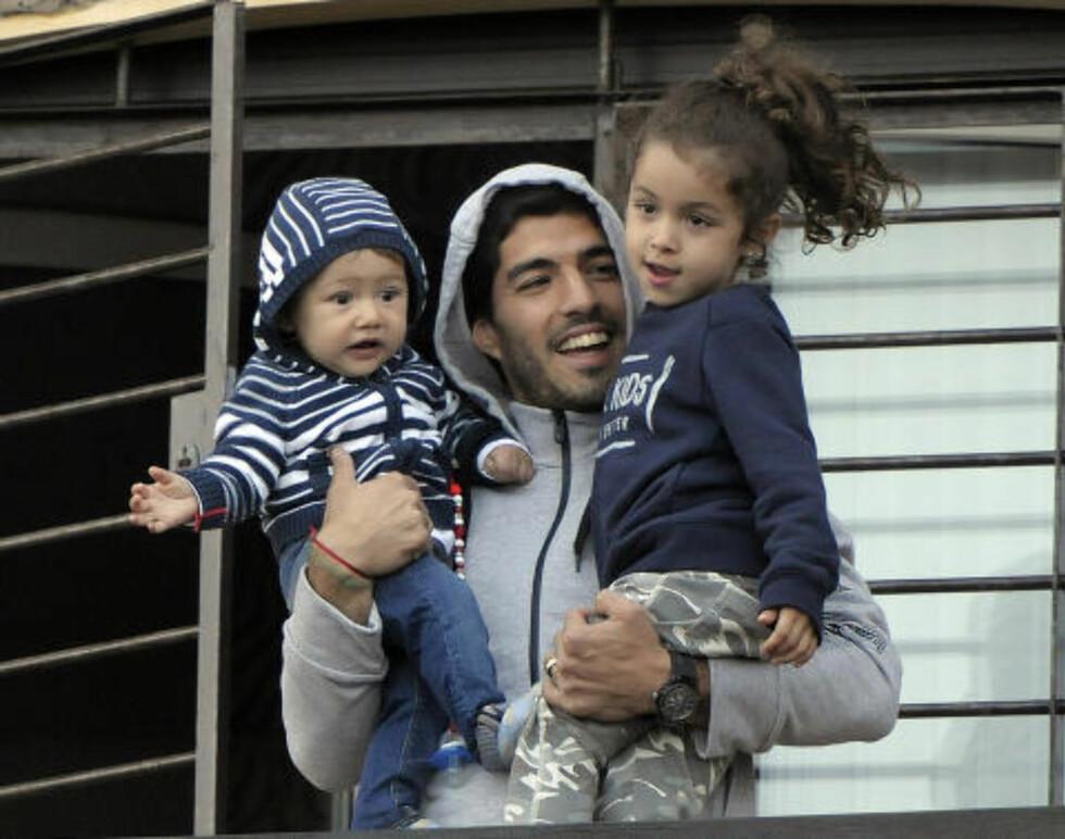 SMILTE: Luis Suárez er utestengt fra resten av VM, men smilte da han vinket til pressen sammen med barna sine i Montevideo i dag. Foto: AP Photo / Matilde Campodonico / NTB Scanpix