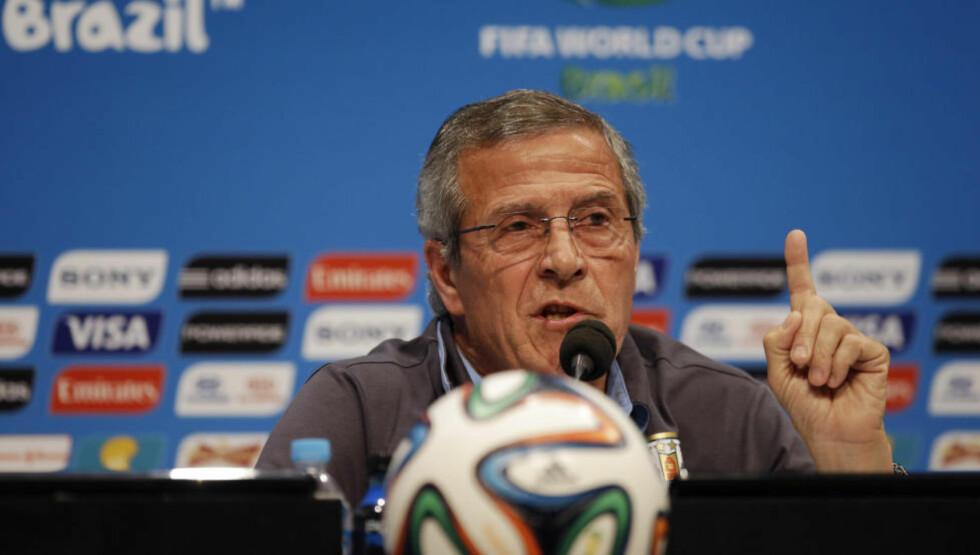 LESTE OPP TEKST: Uruguay-sjef Oscar Tabarez leste opp en lang tekst på dagens pressekonferanse. Så gikk han, uten å si et eneste ord om morgendagens kamp. Foto: AP Photo / Matt Dunham / NTB Scanpix