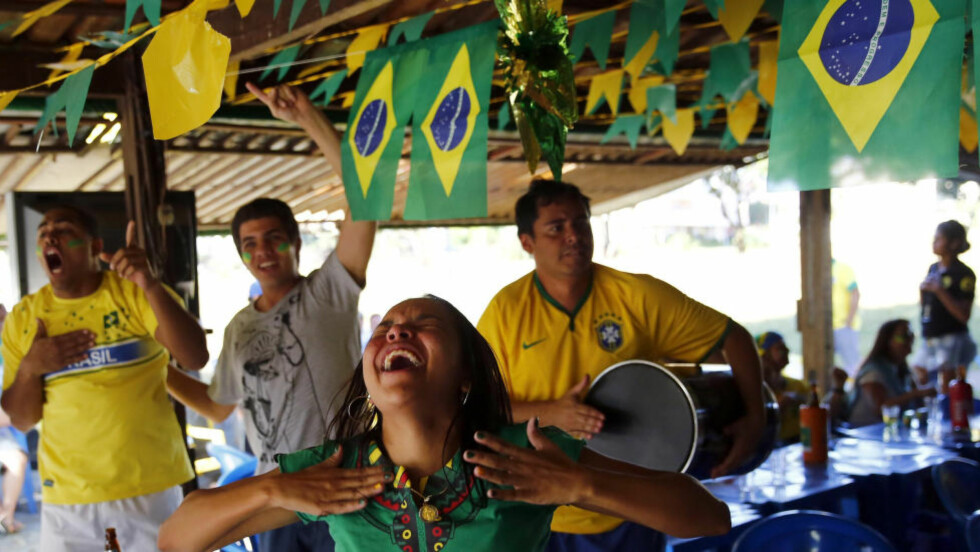 Brazil soccer fans react as they watch their team's victory against Chile during a 2014 World Cup round of 16 game, in a bar in Brasilia June 28, 2014.  REUTERS/Jorge Silva (BRAZIL - Tags: SPORT SOCCER WORLD CUP SOCIETY)
