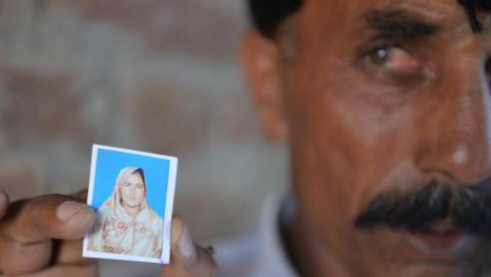 MINNE:  Ektemannen Mohammad Iqbal (46) viser fram bilde av kona Farzana Parveen (25) etter at hun ble steinet til døde av sin egen familie foran høyesterett i Lahore 27. mai i år. Foto: Amir Qureshi, AFP/NTB Scanpix.
