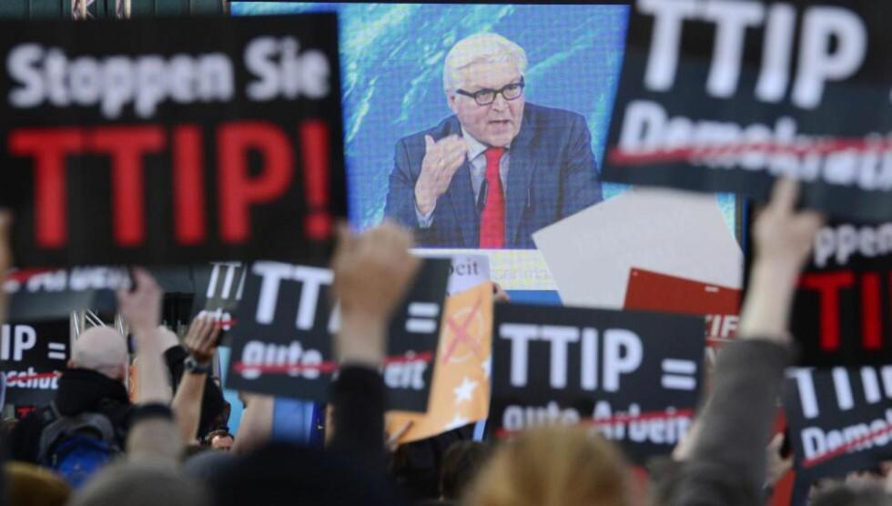 OMSTRIDT:  - Det er mange som frykter at sluttresultatet av avtalen blir et «kappløp mot bunnen», der den laveste standarden blir den gjeldende på begge sider, skriver Gunnesdal. Bildet viser tyske demonstranter mot TTIP, foran en TV-skjerm med Tysklands utenriksminister, Frank-Walter Steinmeier. Foto: NTB Scanpix
