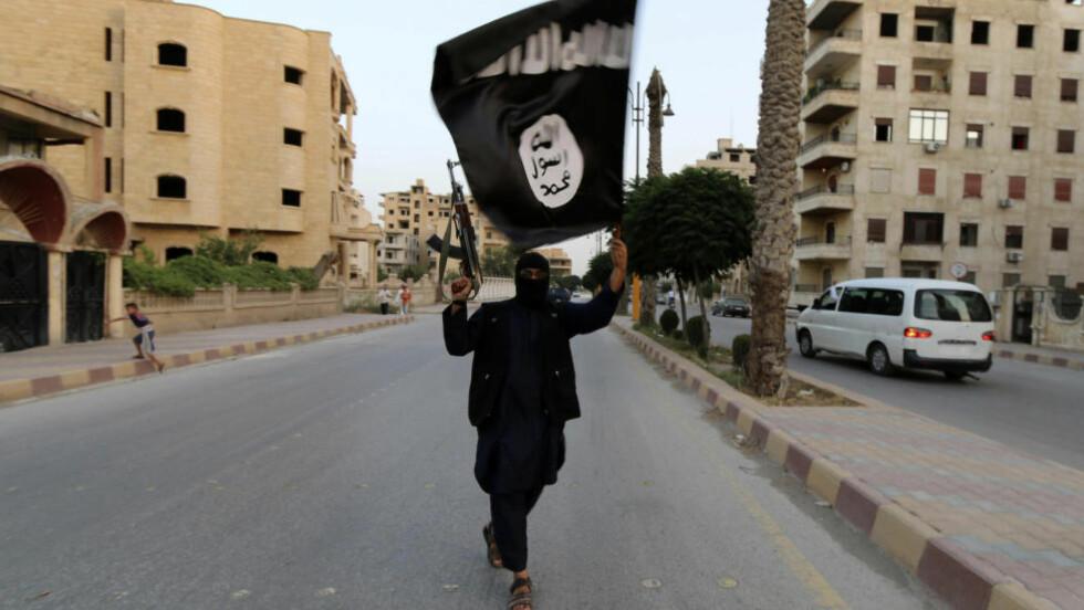 FOR KALIFATET : En tilhenger av kalifatet i byen Raqqa. Religiøs og politisk makt hviler i flagget og våpenet. REUTERS/Stringer Scanpix