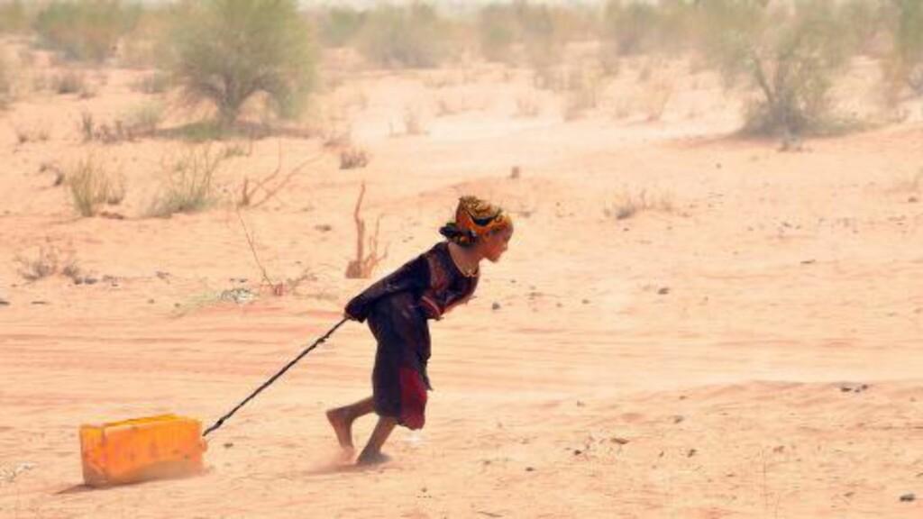 LEVER LIVSFARLIG I ØRKENEN:  På grunn av krig og konflikt har over 60 000 maliere flyktet til nabolandet Mauritania, hvor de må leve et hardt og uverdig liv i ørkenen. Her drar en jente en kanne med vann tilbake til flyktningeleiren Mbere, nær Bassiknou, sør i Mauritania. Foto: Abdelhak Senna / AFP Photo / NTB Scanpix