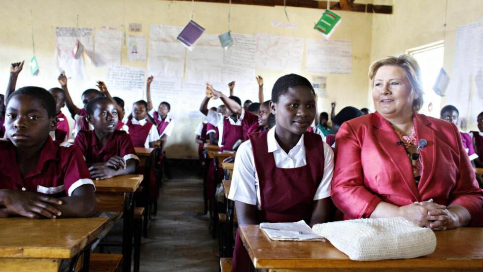 PÅ SKOLEBENKEN Her er Erna Solberg på skolebenken i Nthulu Primary School, på plass ved siden av Prisca Njolombe (16). Under skolebesøket fikk Solberg høre om utfordringene til en landsbyskole i et fattig land der jentene ofte må slutte på skolen for å jobbe eller fordi de føder barn tidlig. Hun hadde med 100 millioner kroner til skolesatsing i distriktet. Foto:Nina Hansen / Dagbladet
