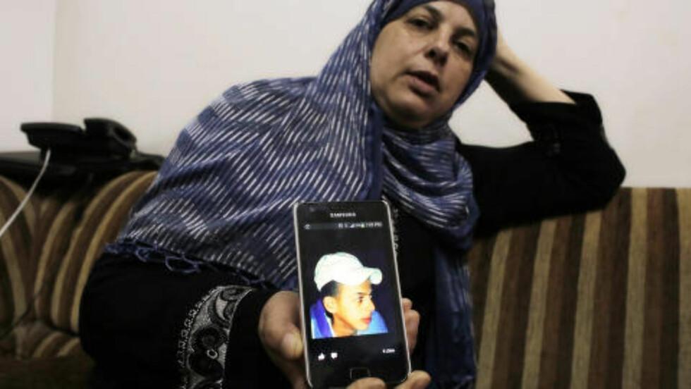 I SORG: Suha Abu Khieder, er mor til palestinske Mohammad *16( som ble drept onsdag. Her viser hun fram et bilde av sønnen. Foto: REUTERS/Ammar Awad