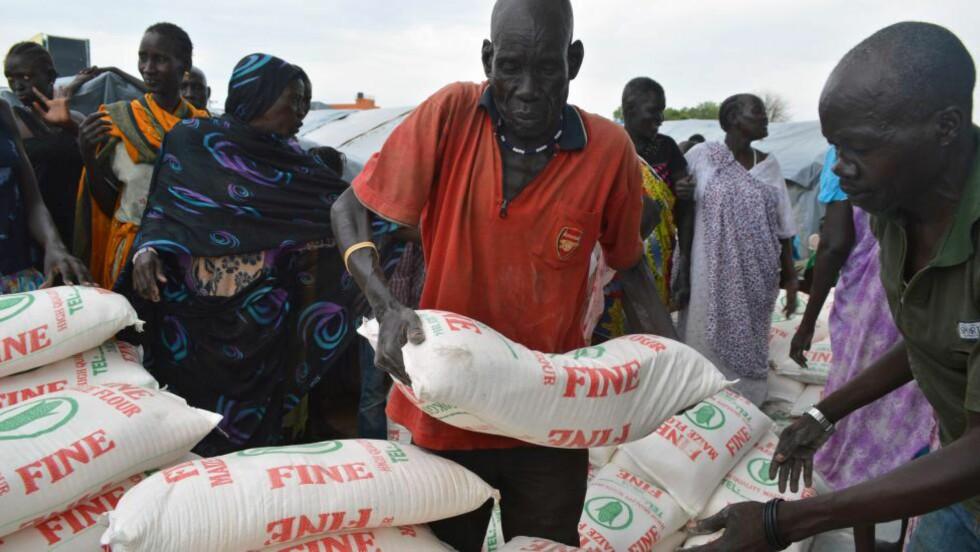 DESPERATE: Flyktninger karrer til seg maismel etter en matutdeling i en flyktningeleir i Juba. Men det er de færreste som får tilgang til mat. Foto: AFP / NTB scanpix