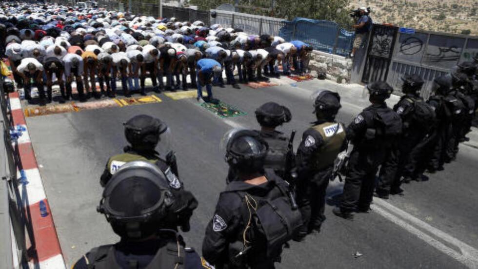 STORE POLITISTYRKER: <7b> Palestinere ber her fredagsbønnen på Ramadans første fredag. Israel har satt inn store politistyrker i Jerusalem for å takle eventuelle demonstrasjoner på grunn av drapet på en 16-årig palestiner, som begraves i dag. Foto: Baz Ratner / Reuters / NTB Scanpix