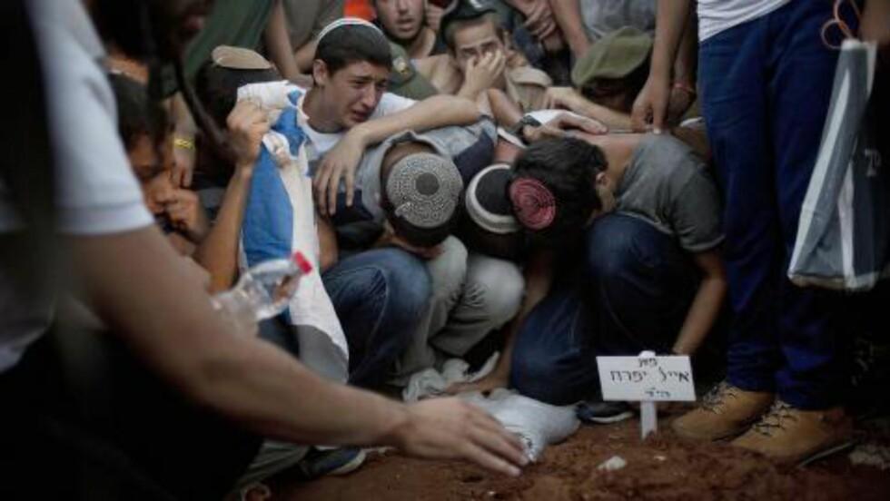 GRAVLA DE TRE ISRELSKE:  Familie og venner sørger her over de tre israelske ungdommene som ble bortført og drept i juni. De ble alle gravlagt i Mondin på tirsdag denne uka. Foto: Ariel Schalit / AP Photo / NTB Scanpix