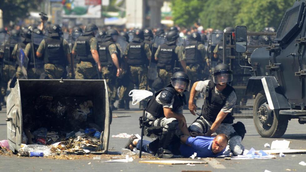 MAKEDONIA: En demonstrant pågripes av politiet under sammenstøt i Makedonias hovedstad Skopje fredag. En rekke personer skal ha blitt skadd. Foto: Reuters / NTB scanpix