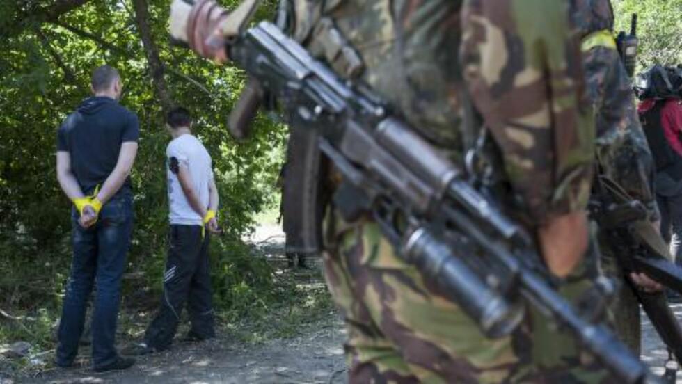 ANHOLDT: Disse hadde våpen i bilene og ble anholdt av ukrainske soldater som har tatt kontroll over Slavjansk og de nærliggende områdene. Opprørerne har flyttet på seg og sier de vil fortsette kampene. Foto:  (AP Photo/Evgeniy Maloletka)