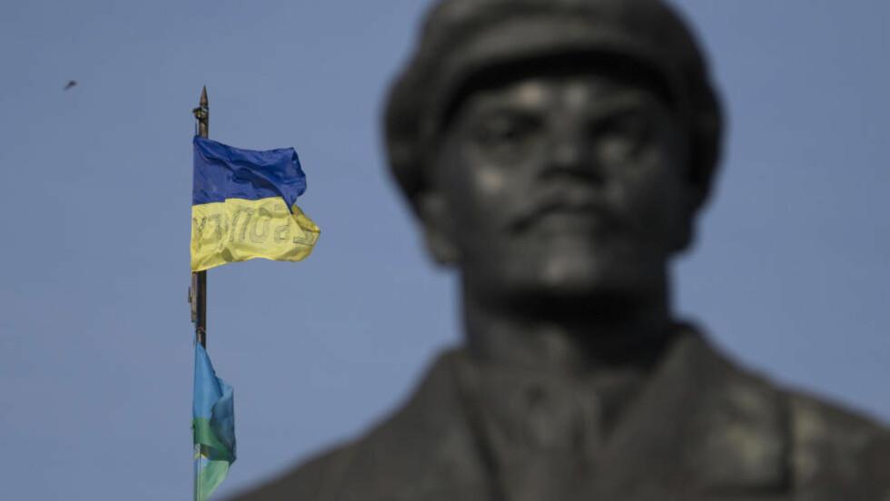 HEISTE FLAGGET: Ukrainske regjeringsstyrker gikk i dag inn og tok kontrollen i Slavjansk. Her har de heist et ukrainsk flagg i nærheten av en regjeringsbygning. Foto: (AP Photo/Dmitry Lovetsky)