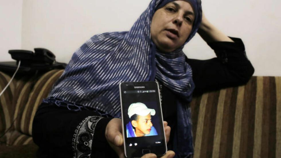 DREPT: Moren til Mohammed Abu Khudair viser frem et bilde av sin drepte sønn. Nå har politiet pågrepet seks israelske høyreekstremister mistenkt for drapet. Foto: REUTERS/Ammar Awad/NTB Scanpix