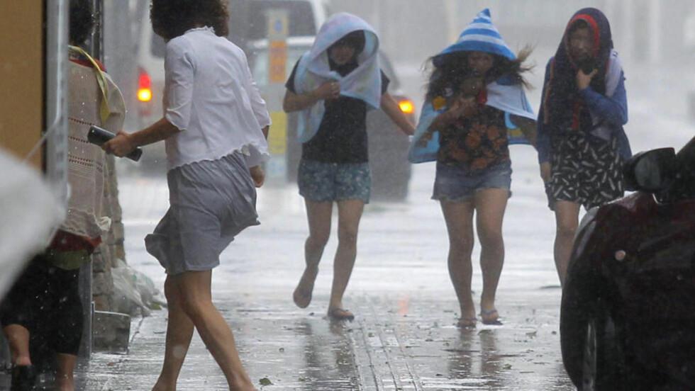 UVÆR PÅ VEI: Sterk vind og regn begynner å treffe Japan med tyfonen Neoguri. Her fra gatene i Naha på Okinawa. Foto: REUTERS/Kyodo