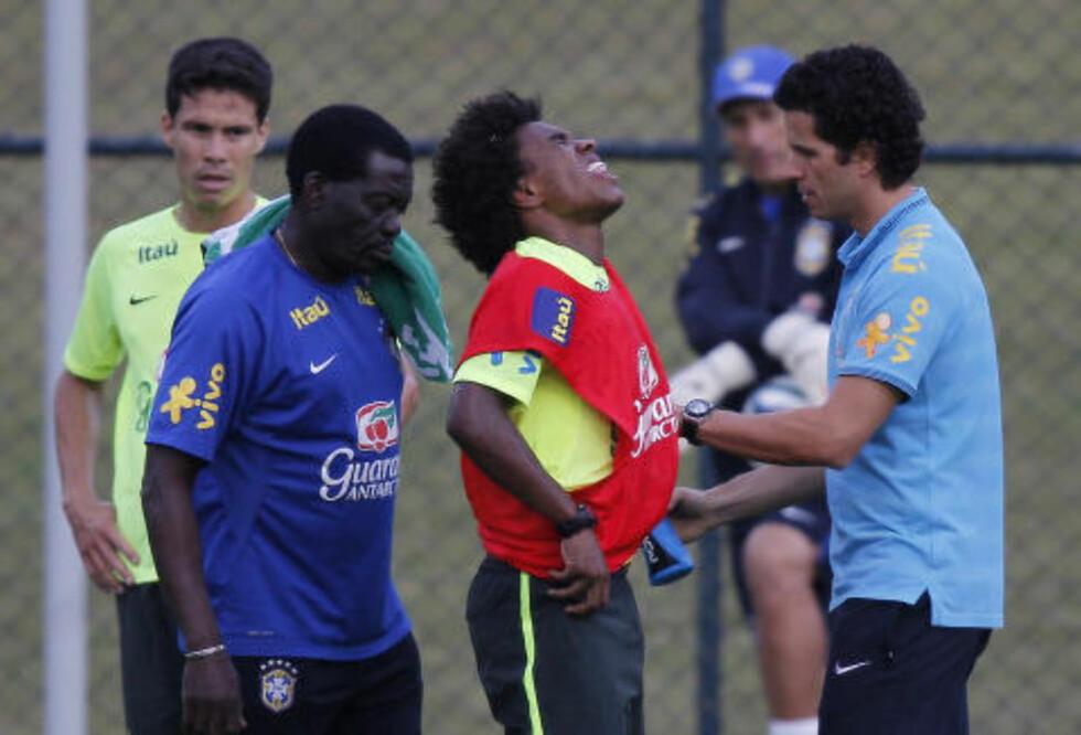 USIKKERHET: Willian ble tatt hånd om av Brasil-doktor Rodrigo Lasmar (t.h.) etter å ha fått en smell i ryggen under lørdagens trening, men er trolig klar i kveld. Så spørs det om han er den spilleren Scolari ønsker å erstatte Neymar med. Foto: Leo Correa, AP / NTB Scanpix
