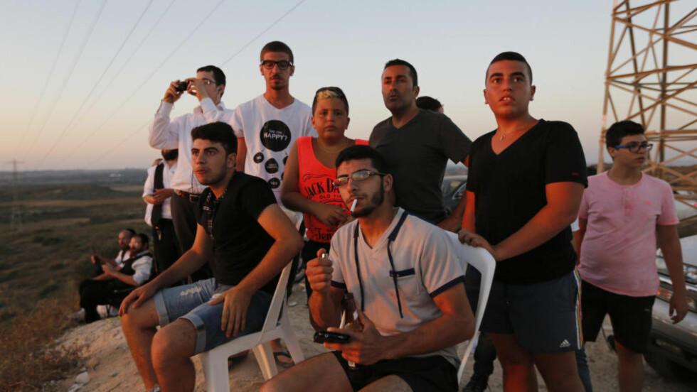 ORKESTERPLASS: Israelere har satt seg til med hagestoler og andre nødvendigheter mens de venter på neste bombenedslag i Gaza, som de har fritt utsyn til. Foto: Lefteris Pitarakis / AP / NTB Scanpix