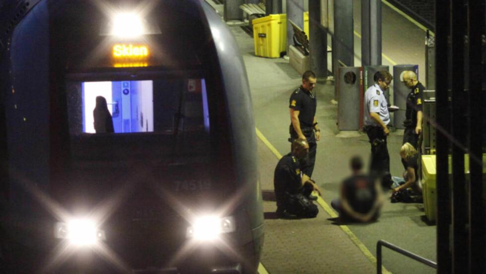 PÅGREPET ETTER KNIVSTIKKING: Her har politiet kontroll på mannen som er pågrepet etter knivstikkingen på toget til Skien. Foto: Joakim Fjeldli