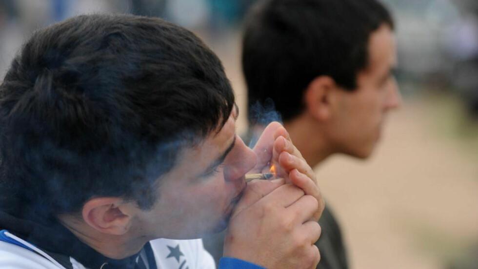 LOVLIG I URUGUAY:  En ung mann fyrer opp en marihuana-sigarett i Uruguays hovedstad Montevido. Uruguay har legalisert hasj under statlig styring: inntil 10 gram i uka pr. bruker, og makspris en dollar pr. gram. Foto: Miguel Rojo, AFP/NTB Scanpix.