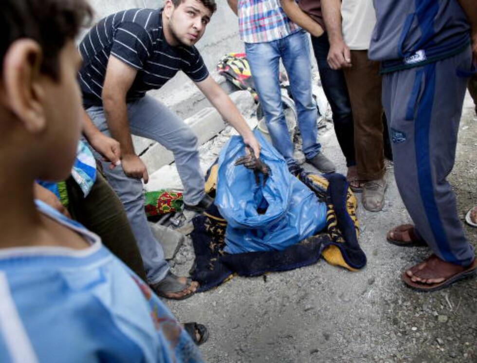 I SISTE LITEN: Abdullah Khalef og familien flyktet fra Tofah-nabolaget for fire dager siden. Lørdag kveld ble slektningene og naboene deres drept da huset deres ble bombet. I den blå sekken ligger Khalefs slektning, Samah. Hun ble gjenkjent på grunn av gifteringen på fingeren. Hun var gravid da hun døde.