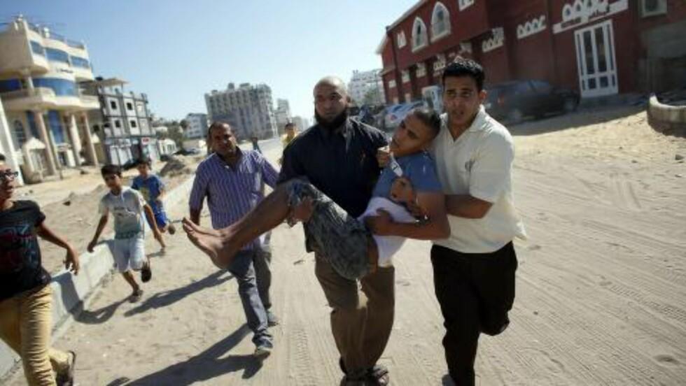 RETT VED HOTELL:  Ansatte ved Hotel al-Deira i Gaza bærer bort en gutt som ble skadd av en israelsk granat fra sjøsiden under fotballspilling på stranda  onsdag ettermiddag. Flere utenlandske pressefolk var på hotellet og ble vitner til det som skjedde. Foto: Thomas  Coex, AFP/NTB Scanpix.