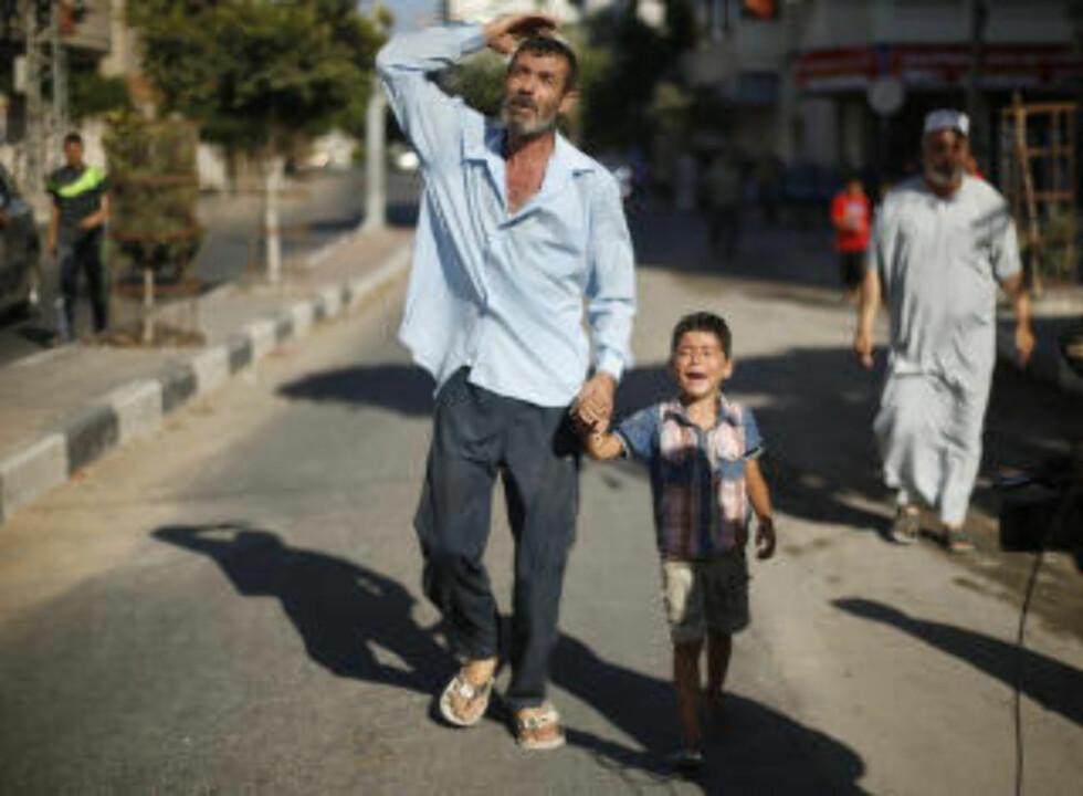 FAR OG BROR I SORG:  Far og bror til en av de palestinske guttene som ble drept mens de spilte fotball, på vei til begravelse samme dag, etter lokal skikk. Alle de fire drepte guttene var i familie med hverandre. Foto: Mohammed Salem, Reuters/NTB Scanpix.