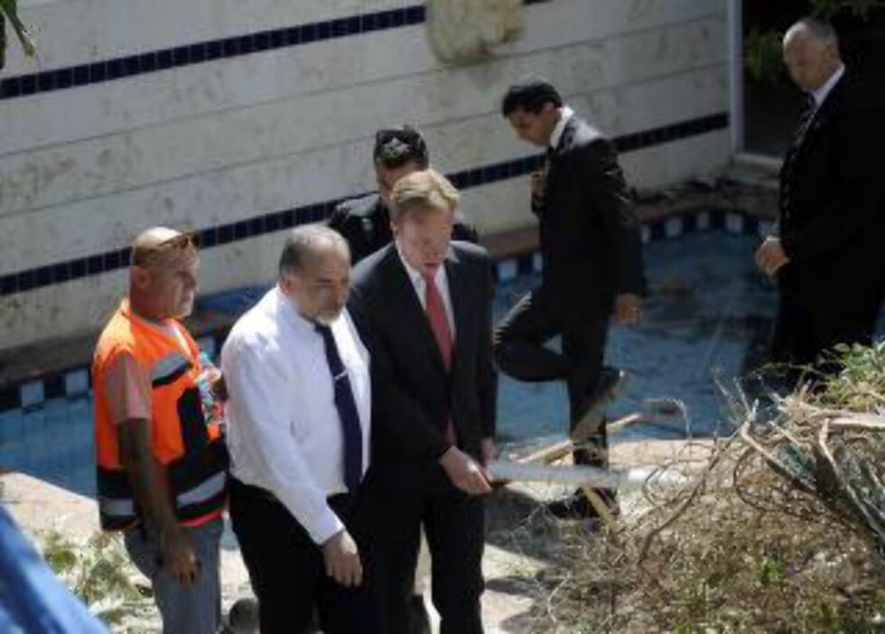 PÅ DEN ANDRE SIDEN:  Utenriksminister Børge Brende på omvisning i regi av sin israelske kollega Avigdor Lieberman (i hvit skjorte) i byen Ashkelon onsdag. Husveggen i bakgrunnen er truffet av en rakett fra Palestina-siden. Foto: David Buimovitch, AFP/NTB Scanpix.