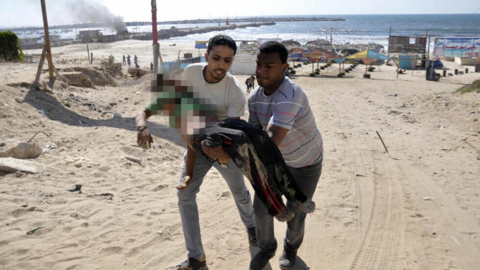 DREPT UNDER FOTBALL-LEK:  En av de palestinske guttene blir båret bort fra stranda ved Gaza by i ettermiddag etter at fem kamerater ble truffet av en israelsk granat. Fire er døde, en alvorlig skadd. Foto: Mohammed Talatene, Reuters/NTB Scanpix.