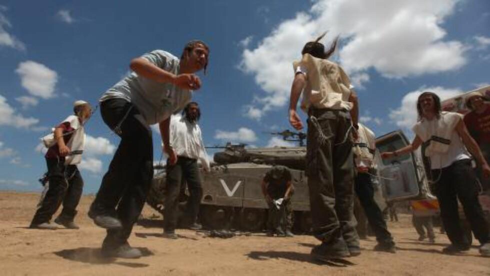 STØTTER SOLDATENE:  Ultraortodokse jøder danser foran israelske stridsvogner som er stasjonert like utenfor Gaza i dag. Foto: Atef Safadi/Epa/Scanpix