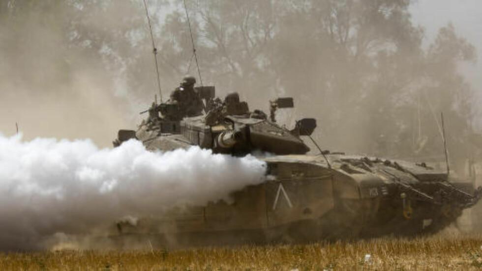 BLODIG KONFLIKT: Over 300 personer har mistet livet og langt flere alvorlig skadet i urolighetene i Gaza. Bildet viser en israelsk tanks nær grensen i dag. En av de israelske soldatenes viktigste oppgaver er å oppdage tunnelene som går fra de palestinske områdene inn i Israel. Foto: Dusan Vranic / AP / NTB Scanpix