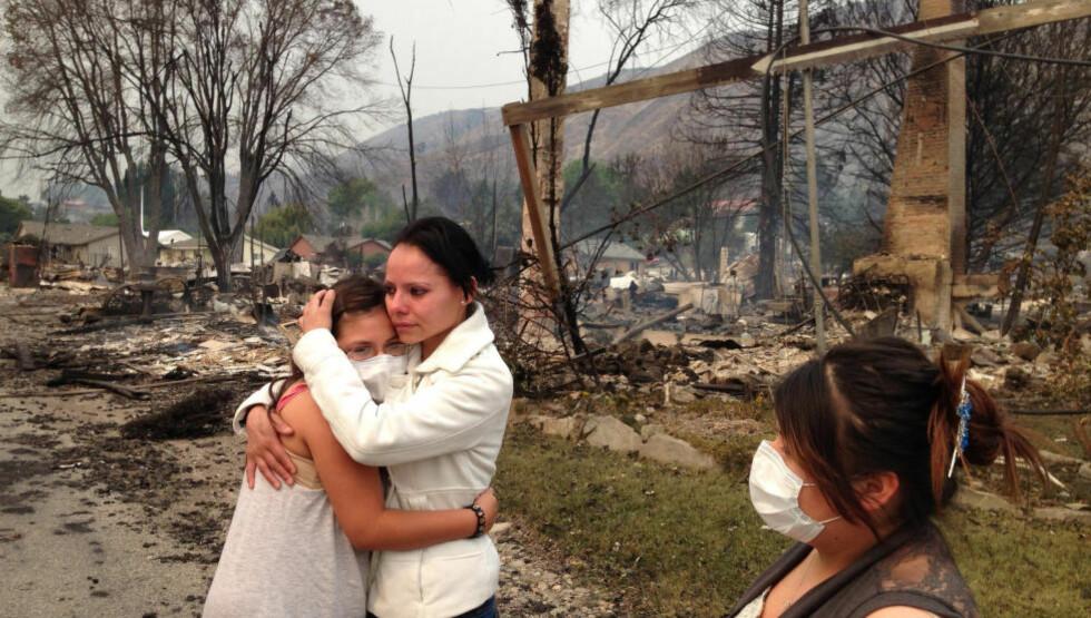 SKOGBRANN: En skogbrann i den amerikanske delstaten Washington resulterte i over 100 nedbrente hjem i byen Pateros. Byen med rundt 650 innbyggere ble evakuert. Emma Franco (i midten) var en av de som mistet hjemmet sitt. Foto: AP Photo/The Seattle Times, Mike Siegel/NTB scanpix