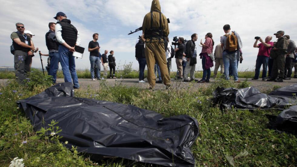 TILDEKKEDE FLYOFRE:  Væpnede separatister i ulykkesområdet øst i Ukraina holder obeservatørerer fra OSSE og media unna. Nå hevder ukrainske myndigheter at opprørerne har fjernet allle de omkomne til et ukjent sted. Foto: Maxim Zmeyev, Reuters/NTB Scanpix.