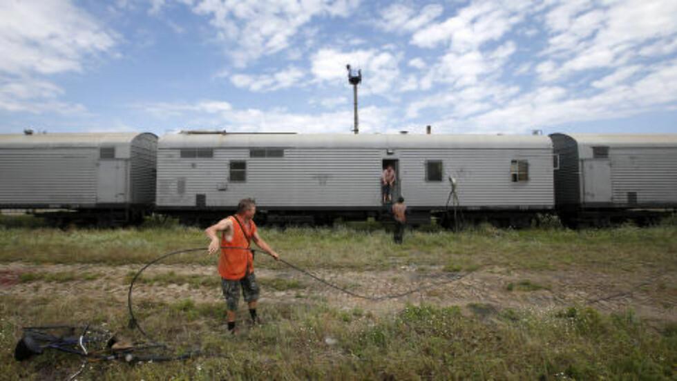 LIKVOGNER:  Jernbanearbeidere bekrefter overfor journalister ved jernbanestasjonen i Torez i Øst-Ukraina at de har lastet omkomne fra flyullykken inn i kjølevognene i bakgrunnen. Foto: Maxim Zmeyev, Reuters/NTB Scanpix.