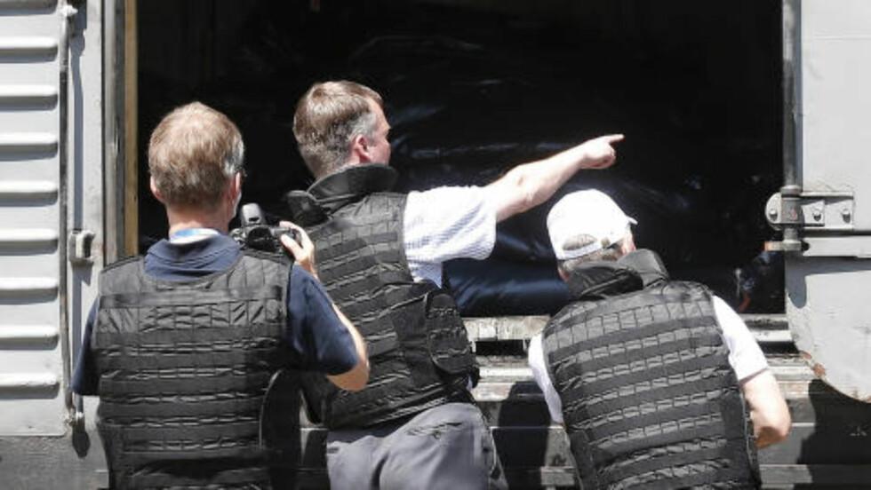 INSPISERER TOGLAST:  Observatører fra OSSE (Organisasjonen for sikkerhet og samarbeid i Europa) sjekker en av togvognene, der døde mennesker i plastsekker er stablet etter flyulykken. Maxim Zmeyev, Reuters/NTB Scanpix.