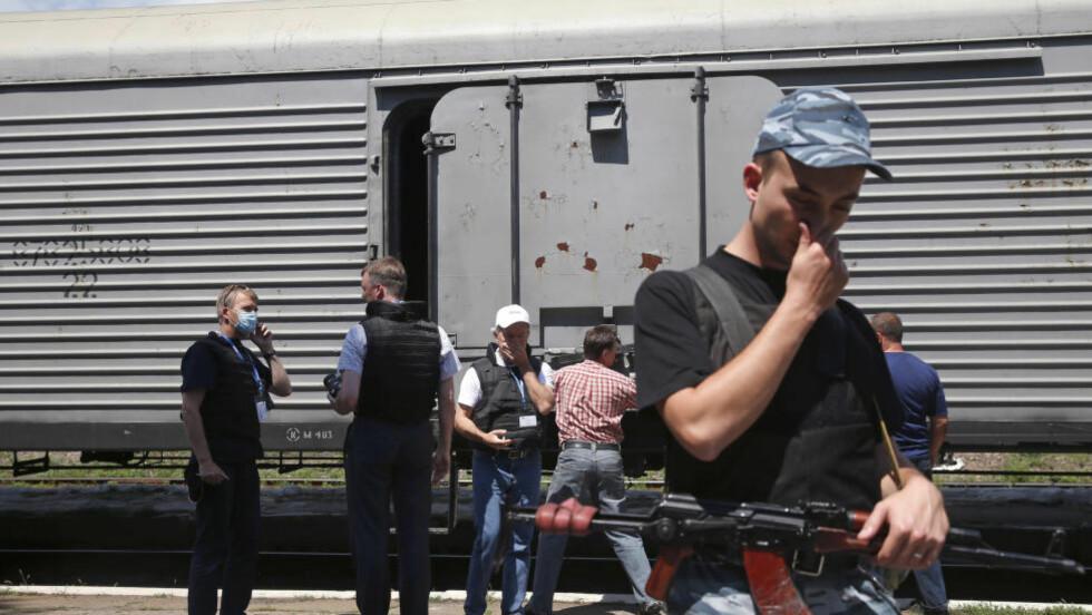 STINKENDE LAST:  En væpnet vakt og observatører fra OSSE i bakgrunnen holder seg for neser på grunn av stanken fra likvognene på toget i stasjonsbyen Torez søndag. Stasjonen ligger 15 kilometer fra ulykkesstedet der det nedskutte Malaysia Airlines gikk ned torsdag ettermiddag. Temperaturene der de omkomne har ligget ute, er rundt 30 grader. Foto: Maxim Zmeyev, Reuters/NTB Scanpix.