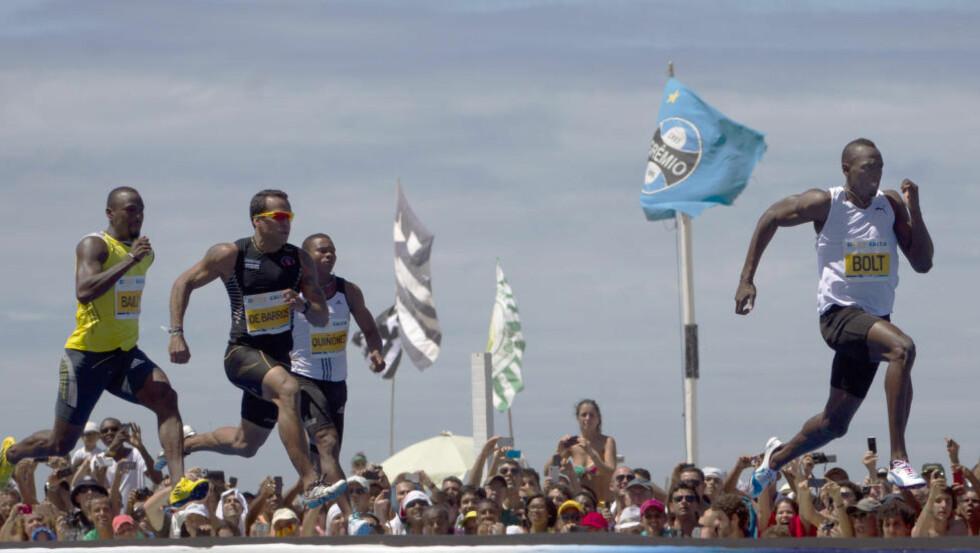 STRANDAS RASKESTE: Usain Bolt (t.h.) på vei mot seieren i «Mano a Mano»-løpet på 150 meter på Copacabana i mars i fjor. Nå skal verdensrekordholderen løpe 100 meter på den berømte stranda i Rio de Janeiro. Foto: Felipe Dana, AP / NTB Scanpix