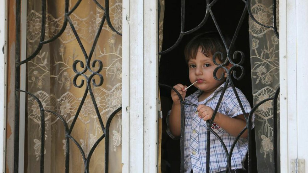 IKKE TRYGT: En liten, palestinsk gutt ser ut fra et vindu i byen Beit Lahiya nord på Gazastripa. FN advarer om at barna betaler den høyeste prisen for Israels militæroffensiv. Foto: EPA/MOHAMMED SABER
