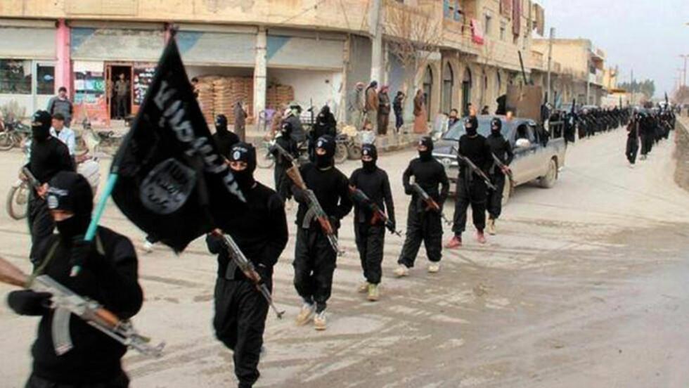 FARLIGE: Her marsjerer Syria-krigere gjennom gatene av Raqqa i Syria. Det er trolig denne gruppen som står bak terrortrusselen mot Norge. Foto: AP Photo/Militant Website/NTB Scanpix
