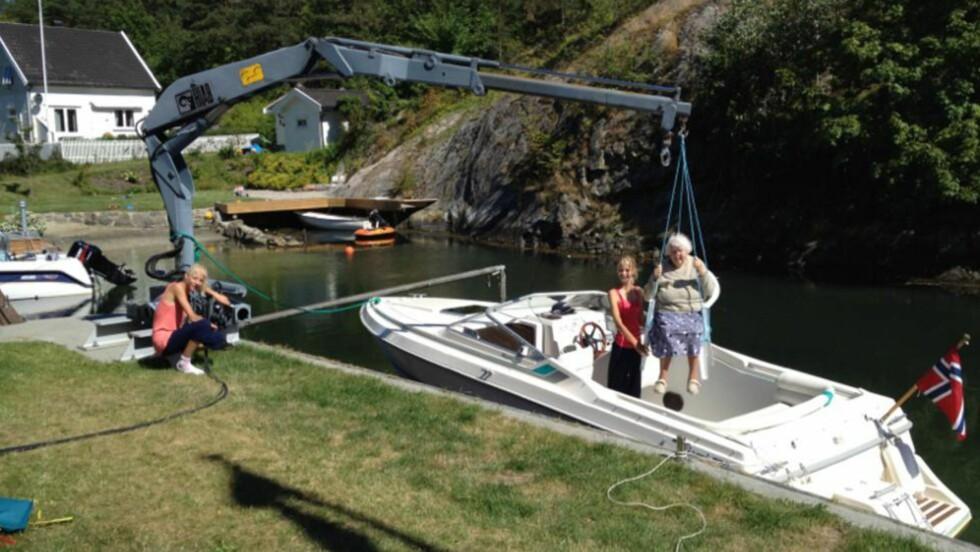 BÅTTUR: For at 89 år gamle Gerd Karlsen, som er dårlig til beins, skal få bli med familien på båttur, bruker sønnen Asbjørn Karlsen en hydraulisk kran til å få henne om bord. Foto: Privat