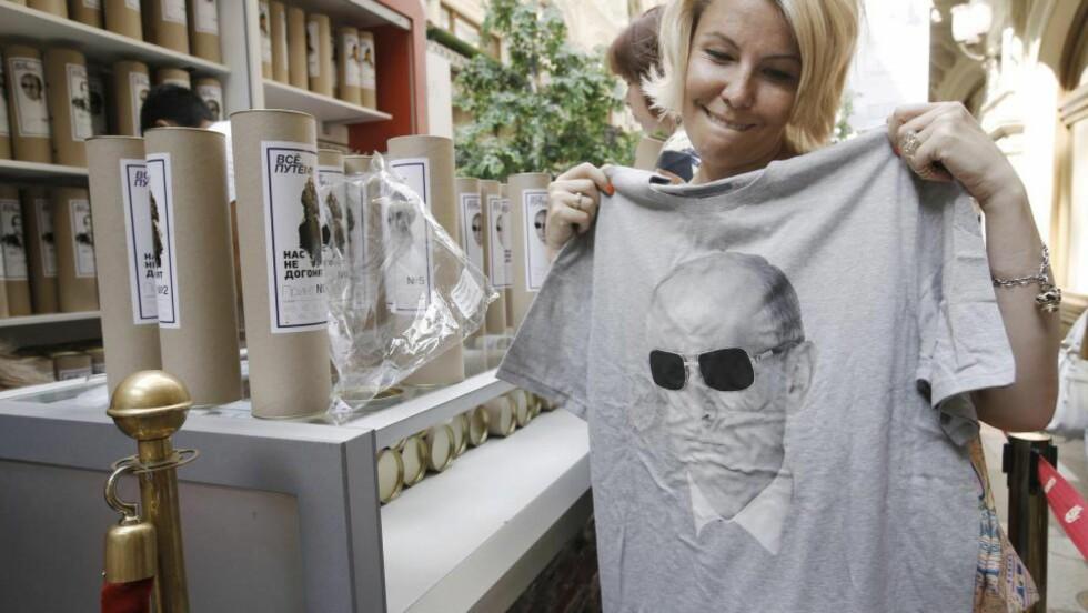 HYLLES: En kvinne holder en t-skjorte med bilde av Russlands president, Vladimir Putin, under et spesialsalg på det statlige kjøpesenteret GUM i Moskva. T-skjortene er skapt av lokale moteskapere som en hyllest til Russlands annektering av Krim-halvøya. Foto: Scanpix