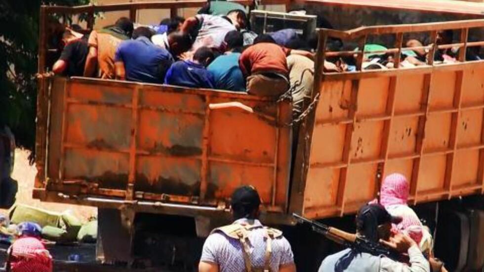 FRAKTES VEKK: Her fraktes IS' ofre vekk i en lastebil før de skal henrettes. Foto: NTB scanpix